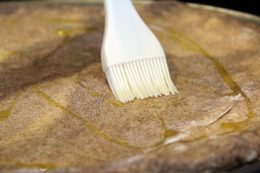 Spread olive oil on crust